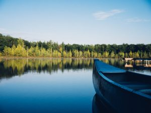 Image of a canoe on water with trees lining the background.
